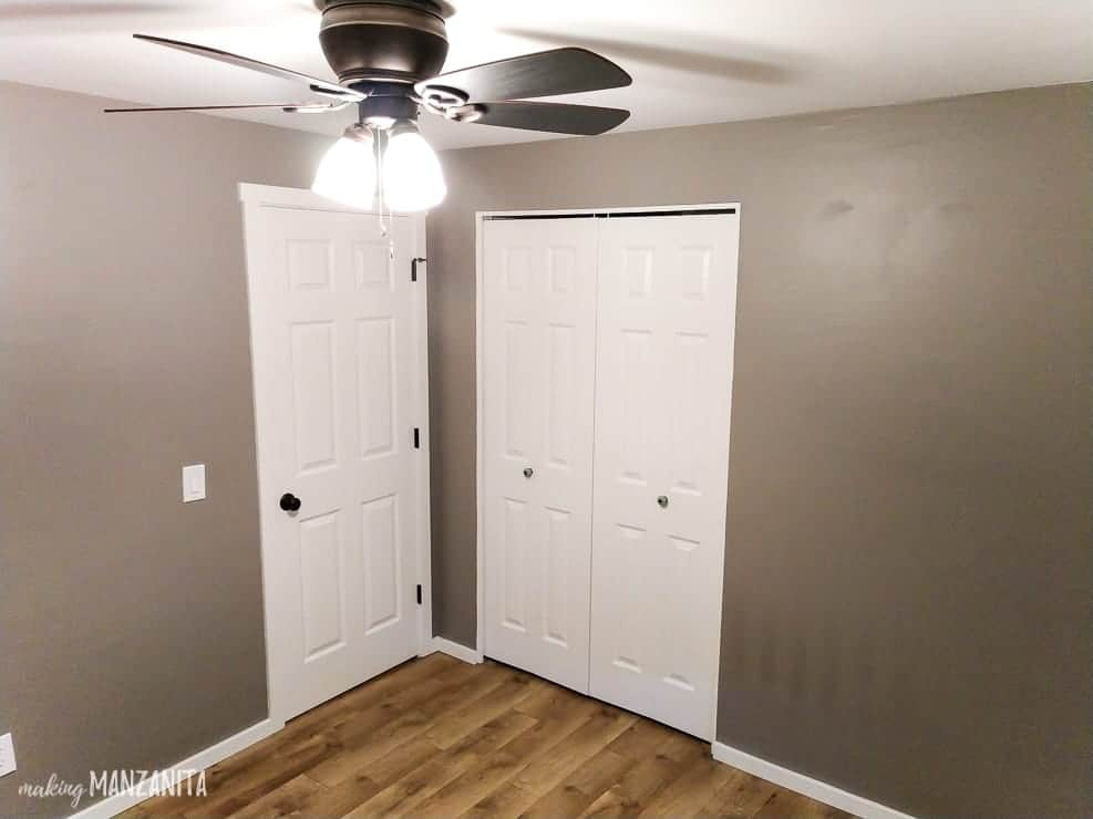 Photo of empty room with gray walls, ceiling fan, hardwood floors and white doors and trim with dark hardware.
