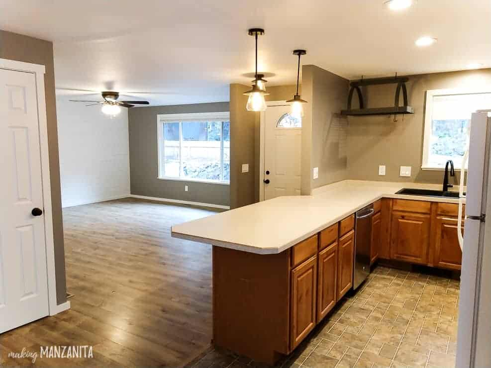 Open concept kitchen with peninsula and light countertops with pendant lights above it that looks into large living room with big window and shiplap wall with gray painted walls everywhere with Fashion Gray paint color from Behr Paint