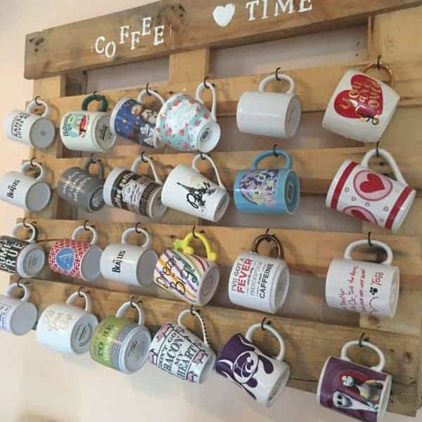 Wood pallet hanging on wall with hooks for coffee mugs