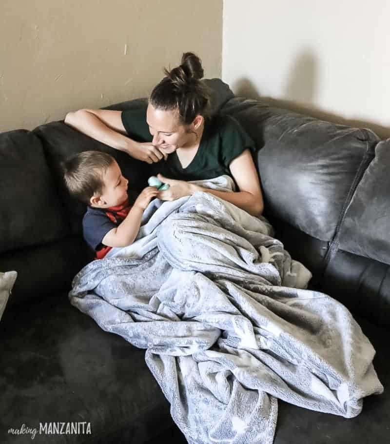Mom and toddler son on gray sectional couch with a gray fuzzy blanket demonstrating a cool and comfortable home