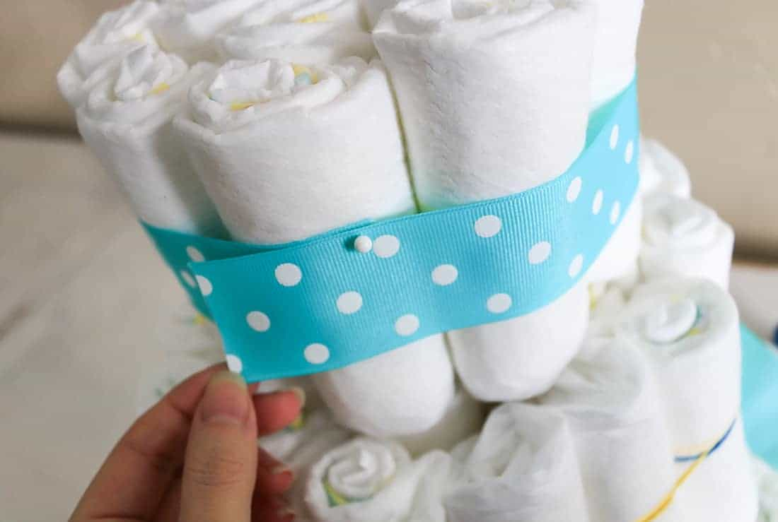 Attaching teal and white ribbon to diaper cake with straight pins to cover up rubber bands