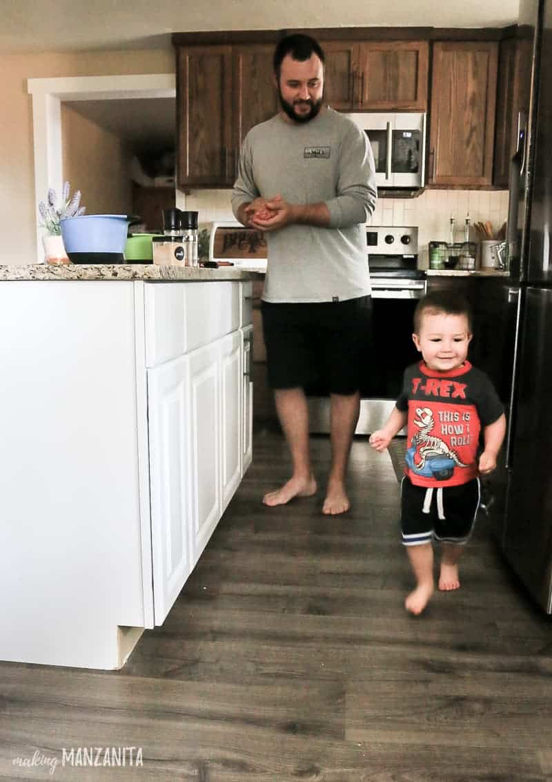 Toddler running around kitchen island in kitchen with father in the background cooking