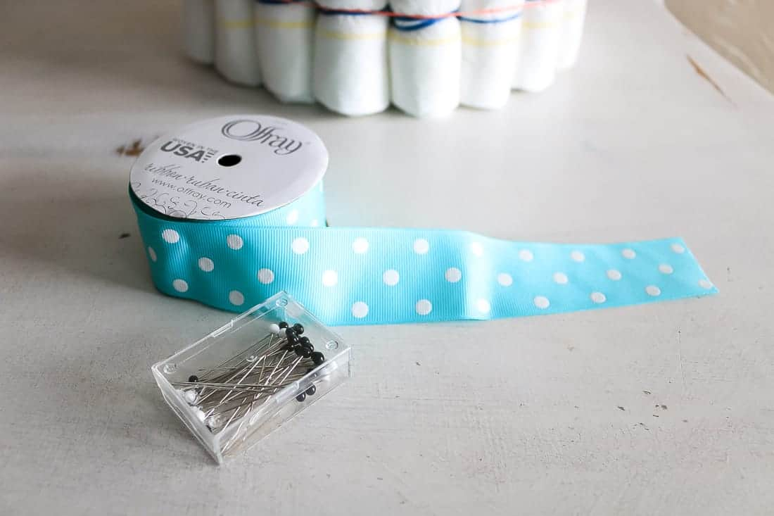 Teal and white polka dot ribbon laying on table with straight pins