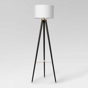 Three legged lamp with black and gold base and white drum shade