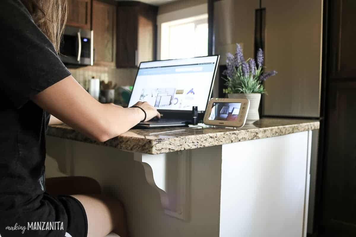 Girl setting at kitchen island on laptop with video baby monitor on counter