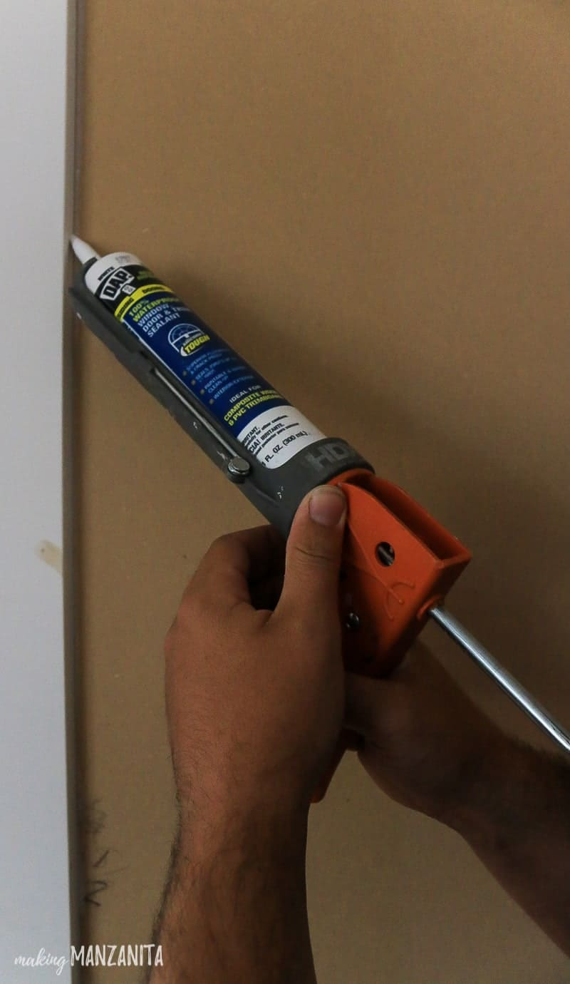 Man adding caulk to board and batten wall seals with caulking gun