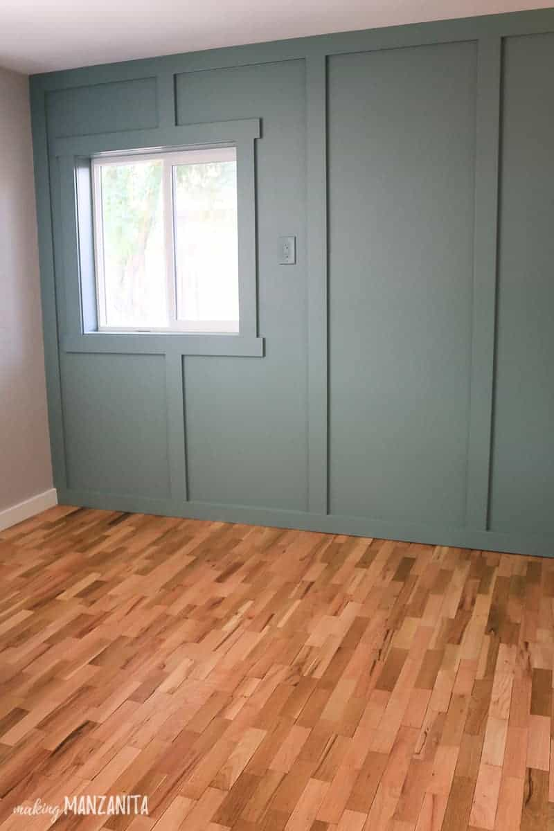 Blue green painted feature wall with board and batten treatment with vertical stripes and installed around a window