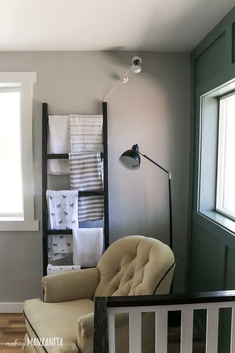 Corner of nursery with blanket ladder leaning against wall with video baby monitor camera mounted to the wall