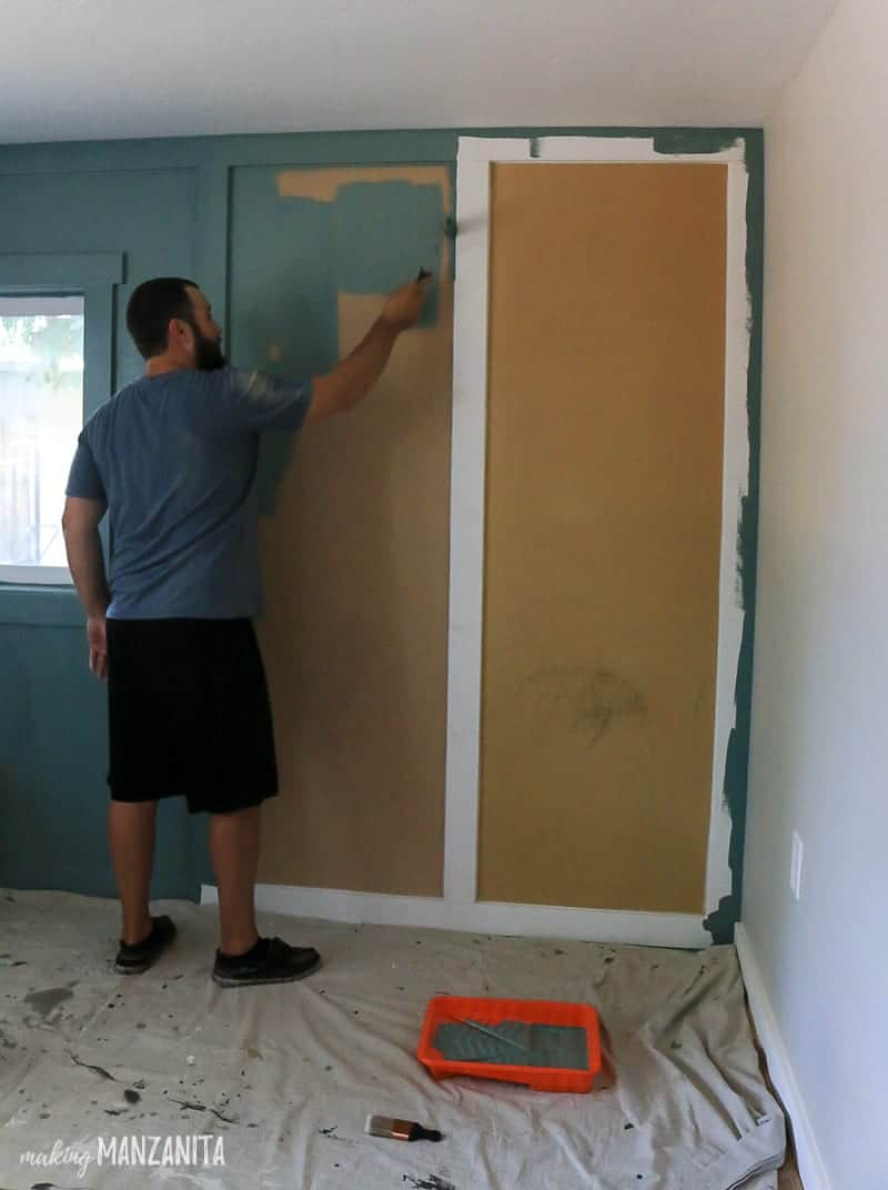 Man painting board and batten feature wall with blue green paint and paint roller
