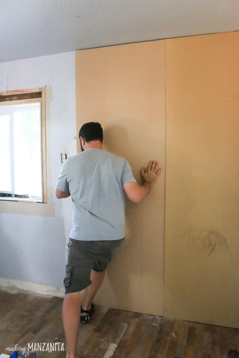 Man pushing MDF panel up and onto a wall