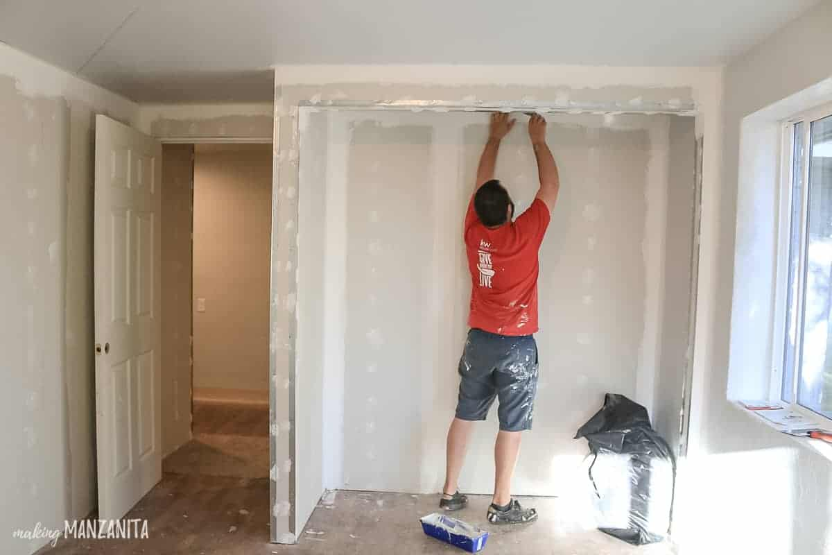 Man taping drywall joints on new walls