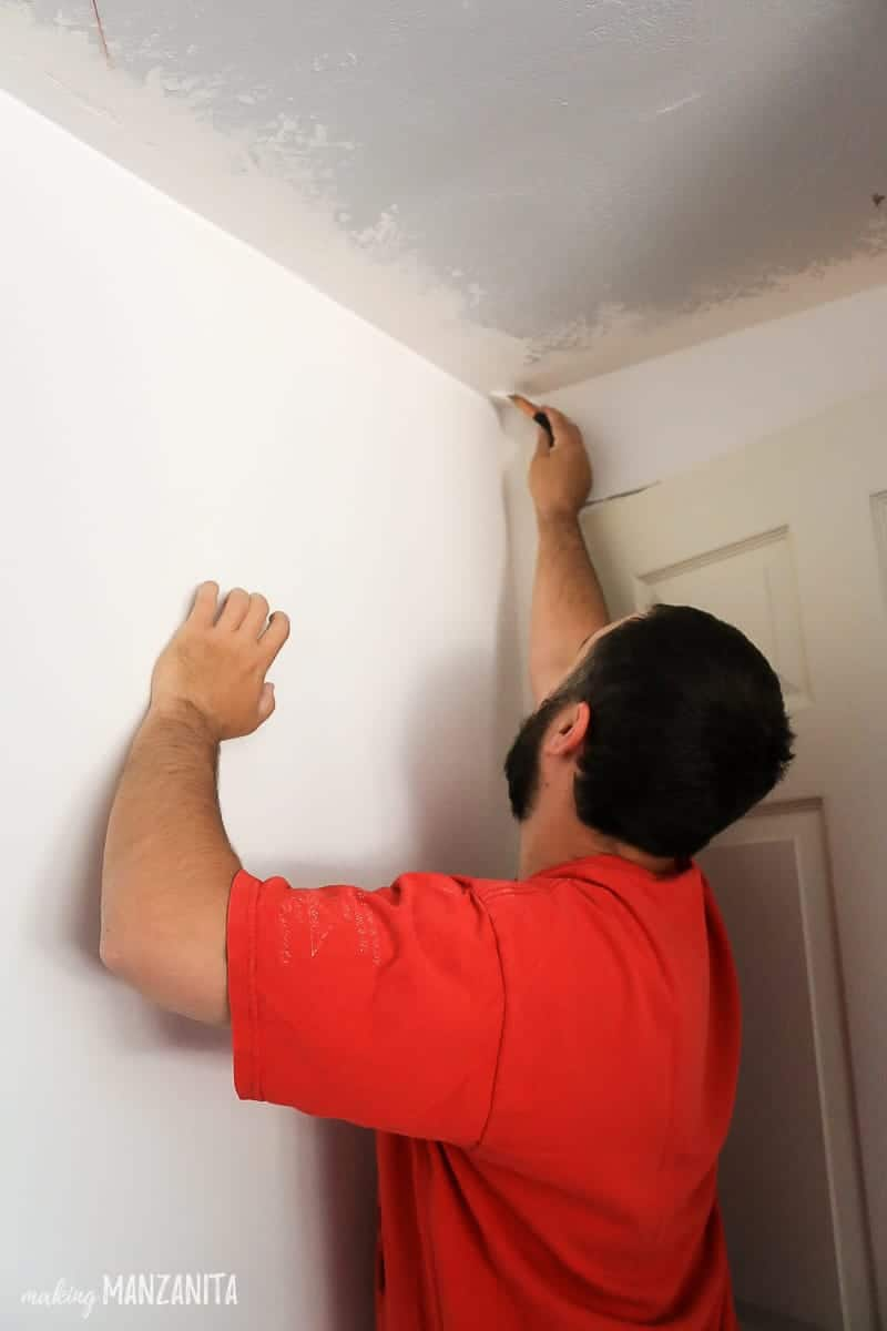 Man painting ceiling corner with paint brush