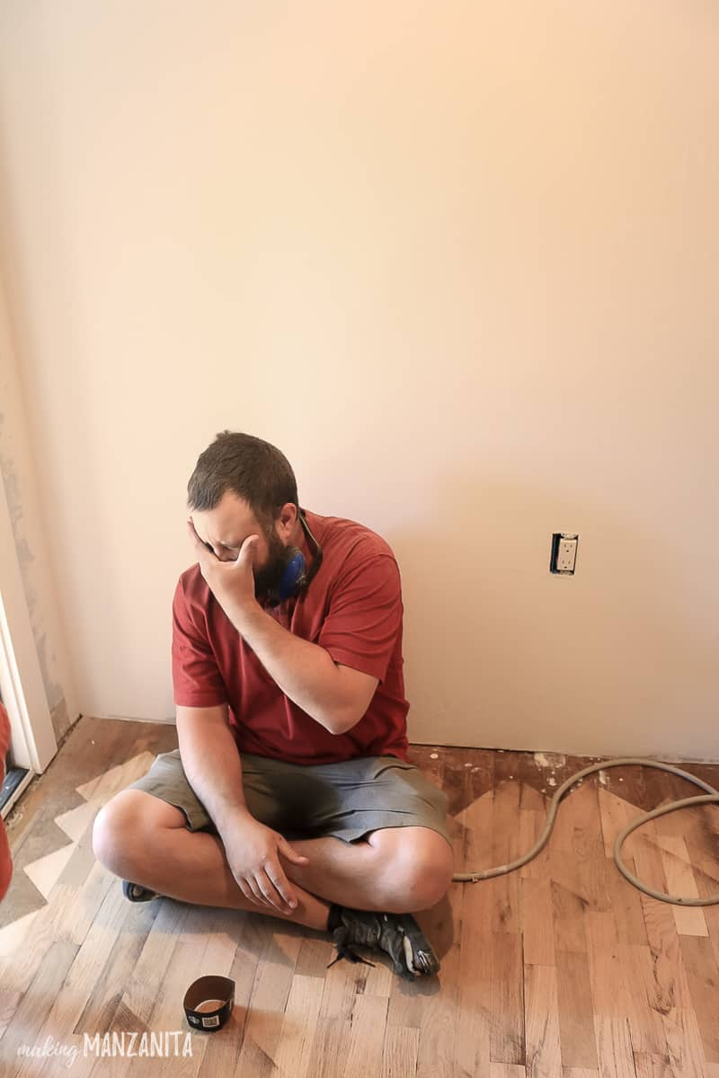 Man sitting on the floor exhausted and covering his face with his hand