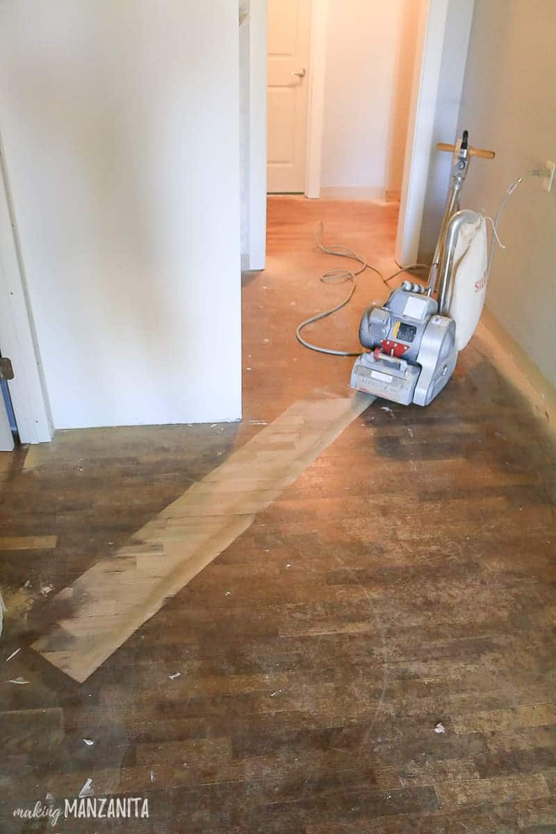 Floor sander on hardwood floors with one stripe sanded on floors diagonally