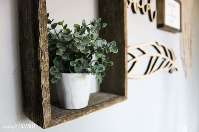 Faux plant on barnwood shelf