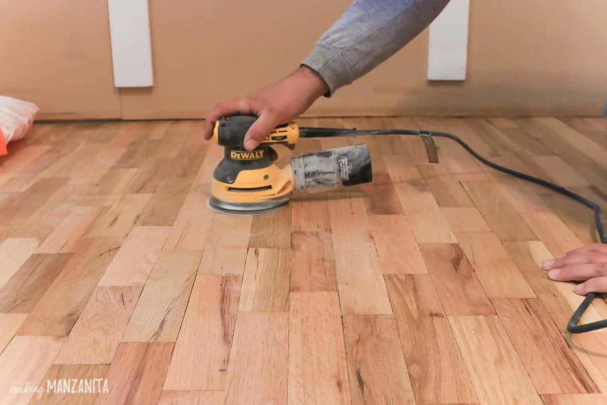 Man using orbital sander on hardwood floors between coast of floor finish
