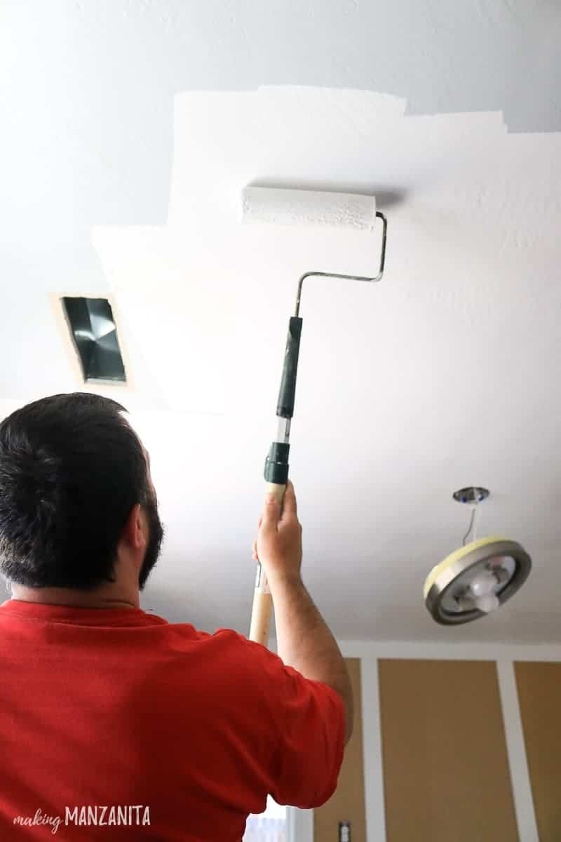 Man rolling white paint on to a ceiling