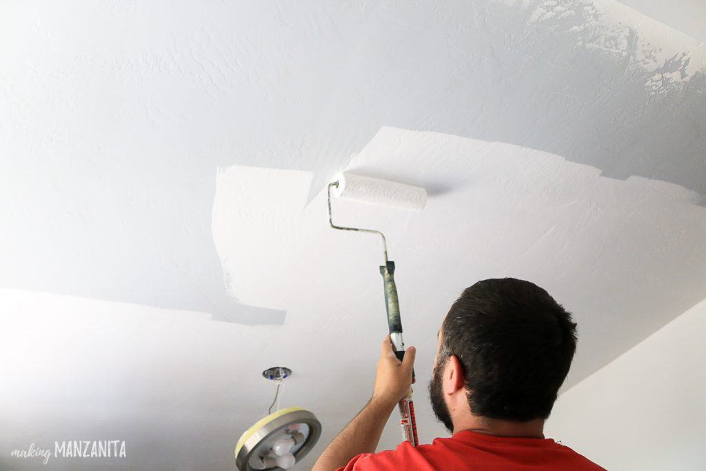 Man rolling white paint onto ceiling with paint roller