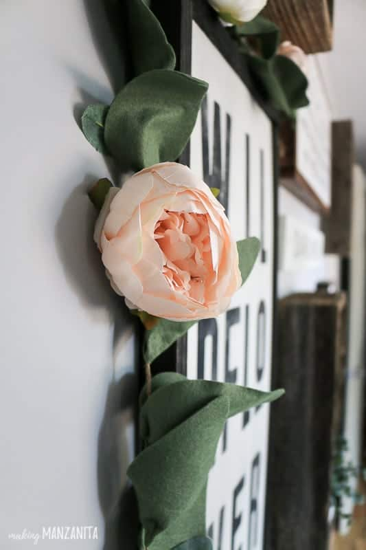 Peony garland hanging on farmhouse sign in gallery wall in baby girl nursery
