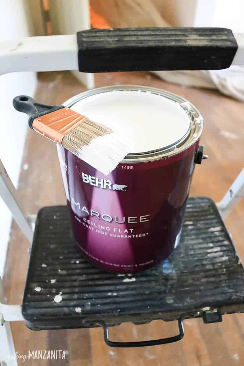 Bucket of Behr Marquee paint sitting on step stool with paint brush