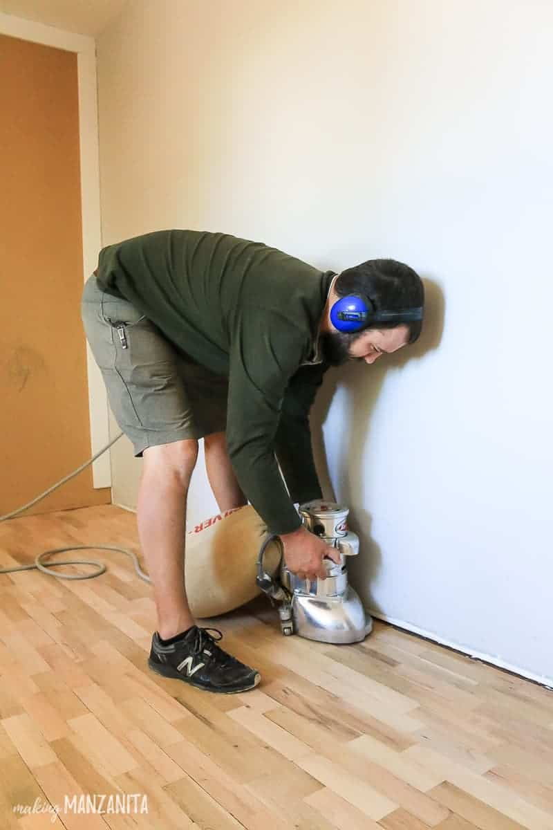 Man holder floor edger to sand edges of hardwood flooring
