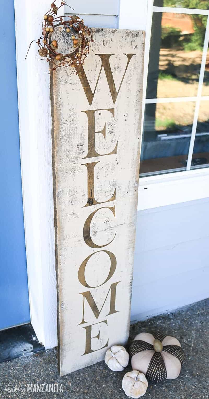 Rustic fall welcome sign make with stencils and styled on front porch