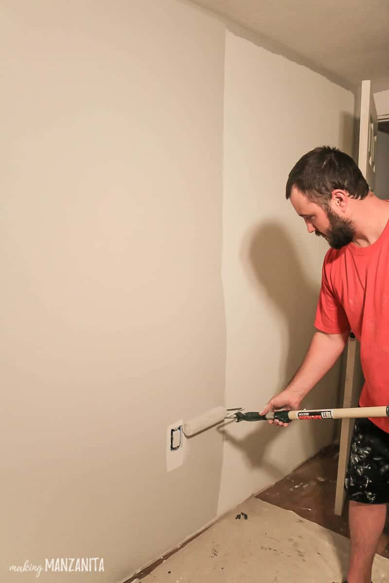 Man rolling gray paint on wall with paint roller