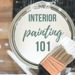 Paint bucket sitting on stool with paint brush with text overlay that says interior painting 101
