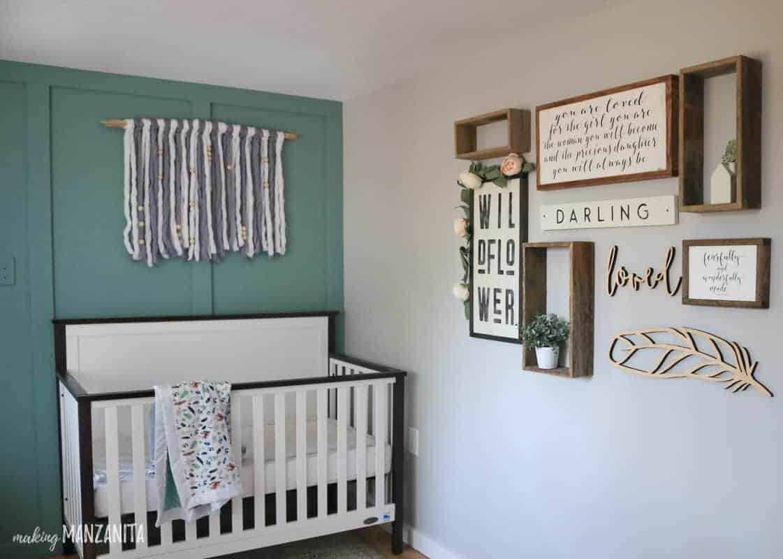 Boho nurery with modern farmhouse crib with green board and batten wall with yarn hanging and rustic gallery wall art
