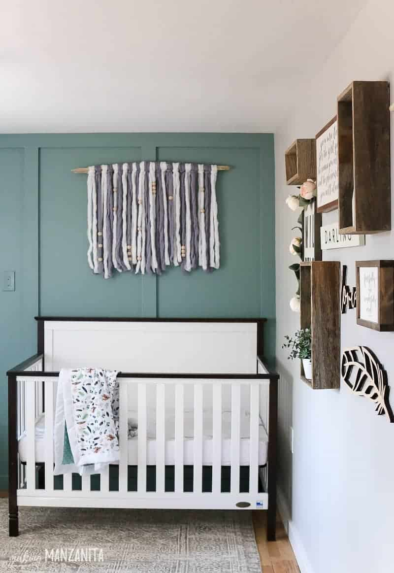 White crib with black trim in front of a blue green board and batten wall with yarn wall hanging
