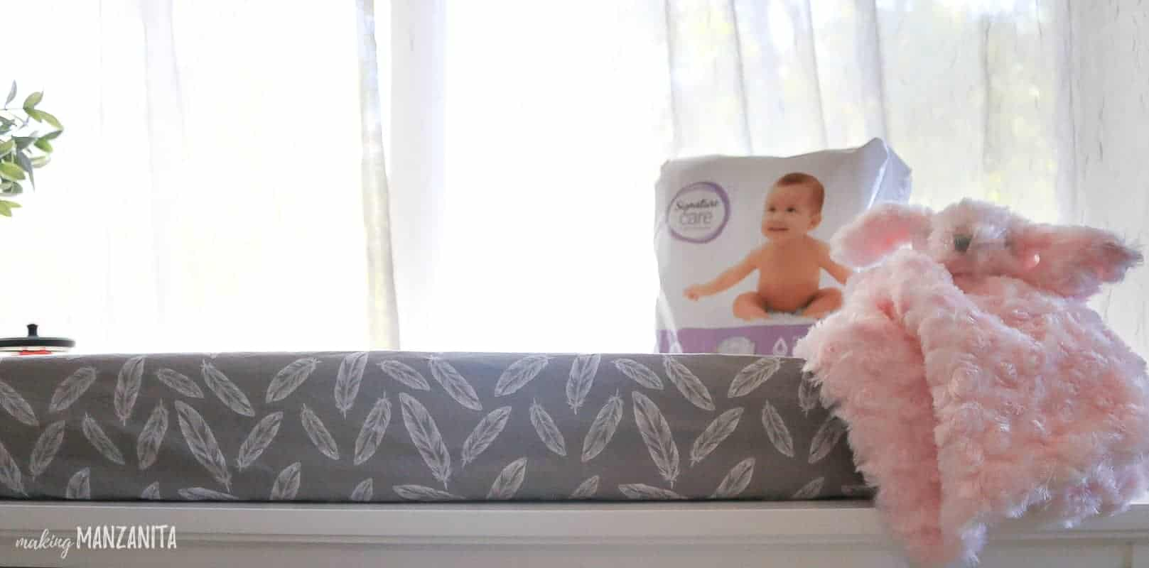 Changing pad with gray and white feather cover sitting on top surface of dresser with package of diapers on top
