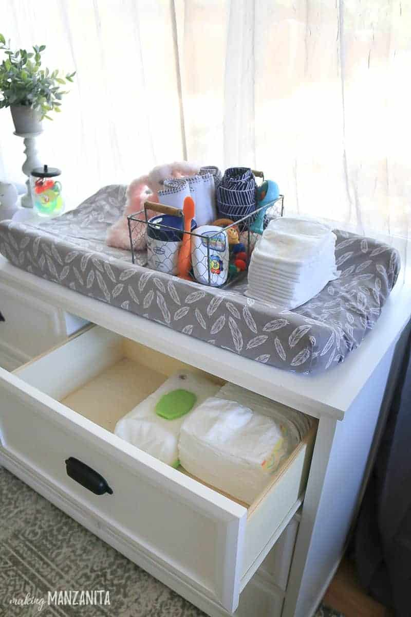 Dresser drawer open showing diapers and wipes with changing pad on top and basket full of diaper changing supplies