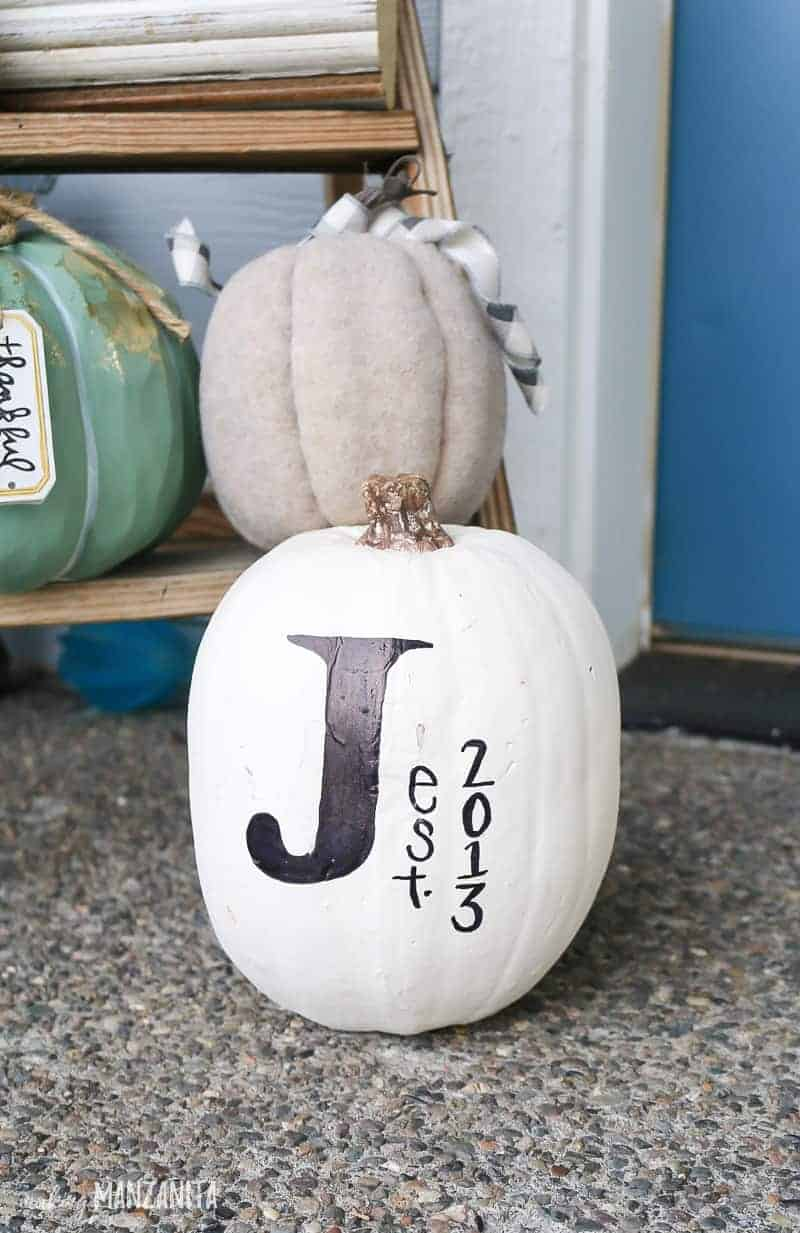 White pumpkin with a big black J written on it sitting on ground in front of wooden ladder with pumpkin decorations.