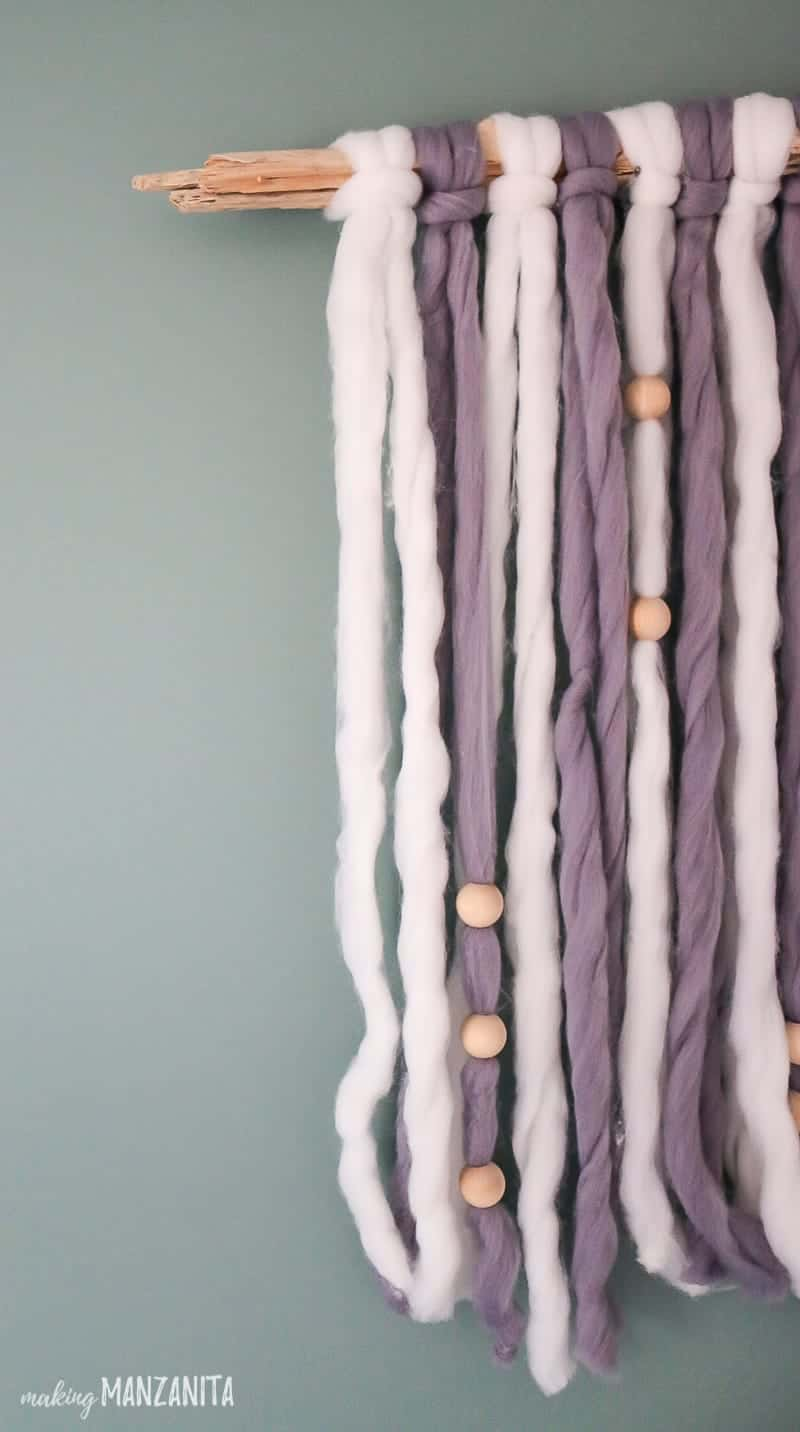 Zoomed in shot of the edges of a DIY yarn wall hanging made with driftwood, chunky yarn and wood beads hanging on green wall