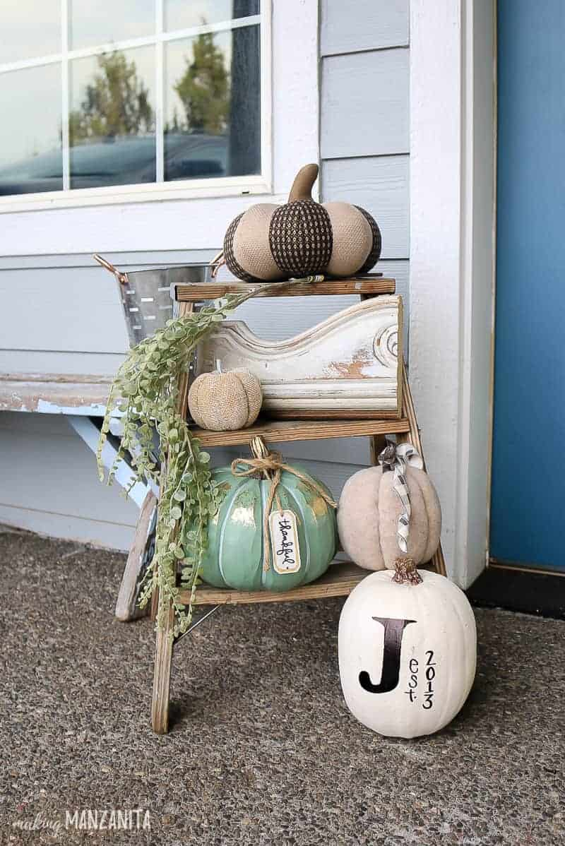 Farmhouse style front porch decorations on antique wooden latter with pumpkins and greenery