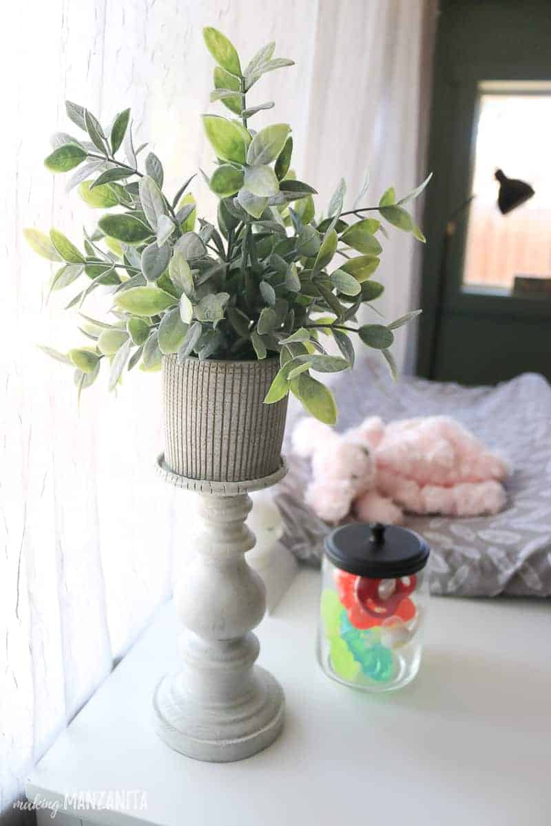 Faux plant on candle holder sitting on top of changing table