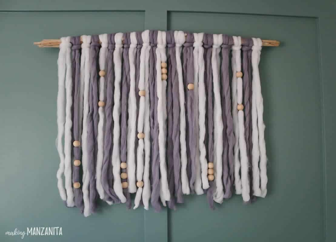 Gray and white yarn looped around driftwood as wall decor hanging on green wall