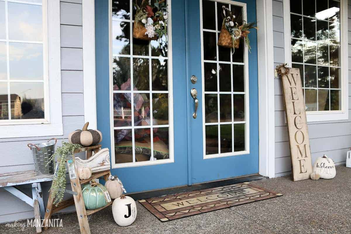 Glass front doors on front porch with fall decorations including a small wooden ladder with pumpkins, fall door baskets with flowers and wooden welcome sign