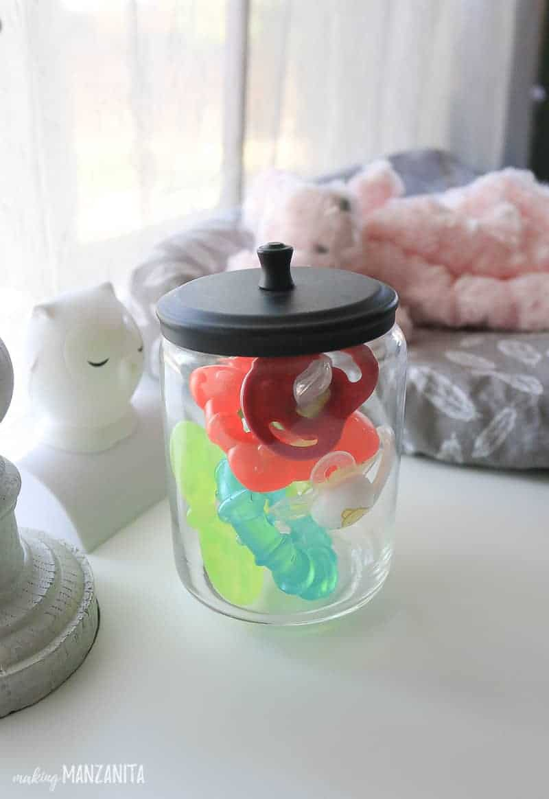 Glass jar full of pacifiers and teethers with lid sitting next to changing pad and night light