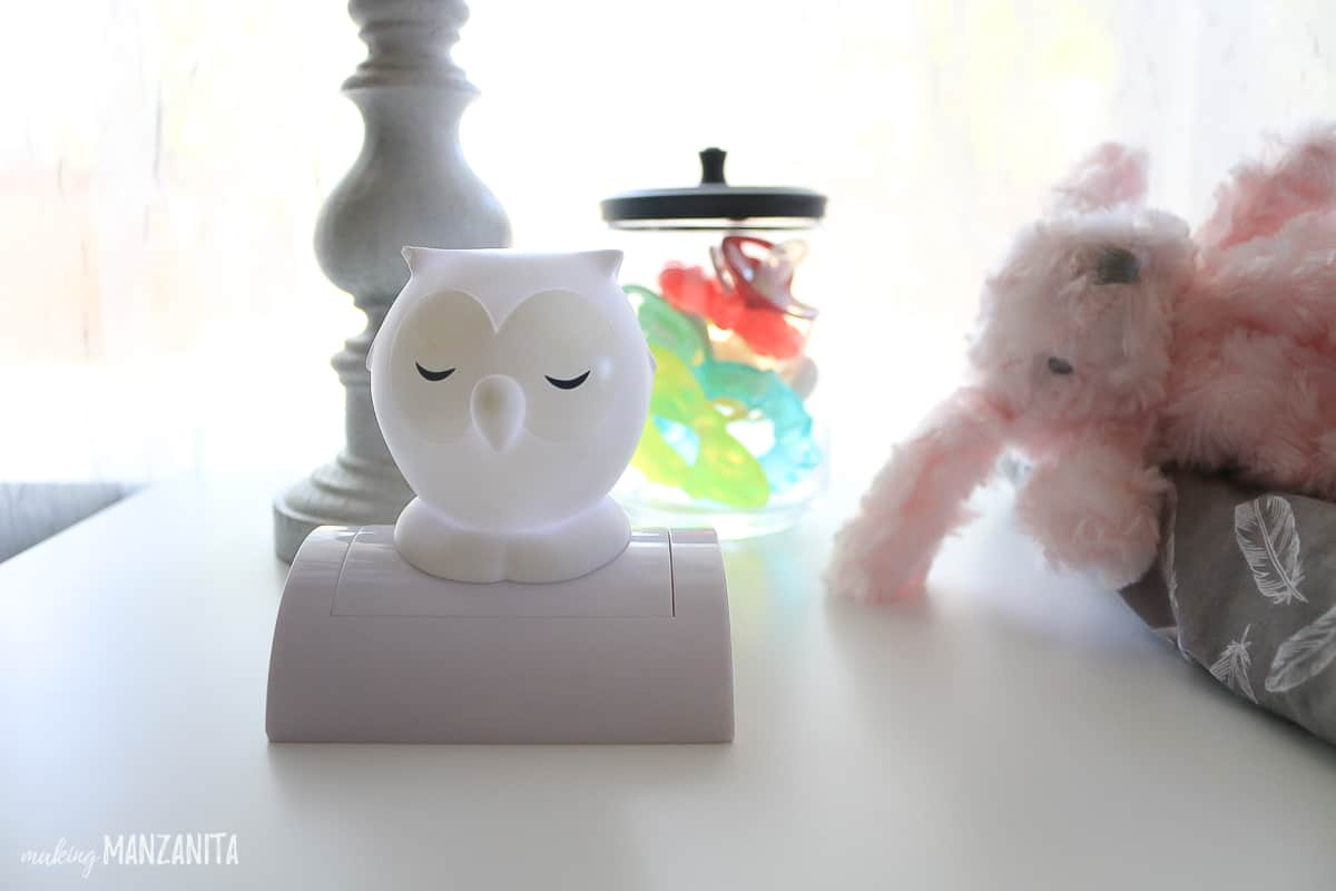 Push on owl nightlight sitting next to jar of pacifiers and pink stuffed animal