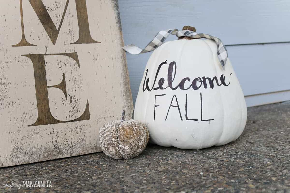 Welcome fall written on white pumpkin in black lettering sitting on ground next to large wooden welcome sign