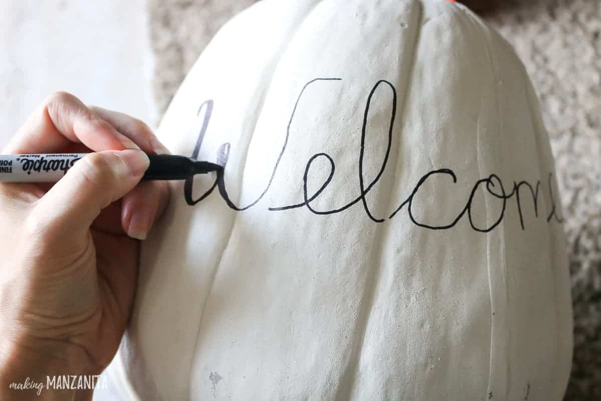 Sharpie writing Welcome on white painted pumpkin