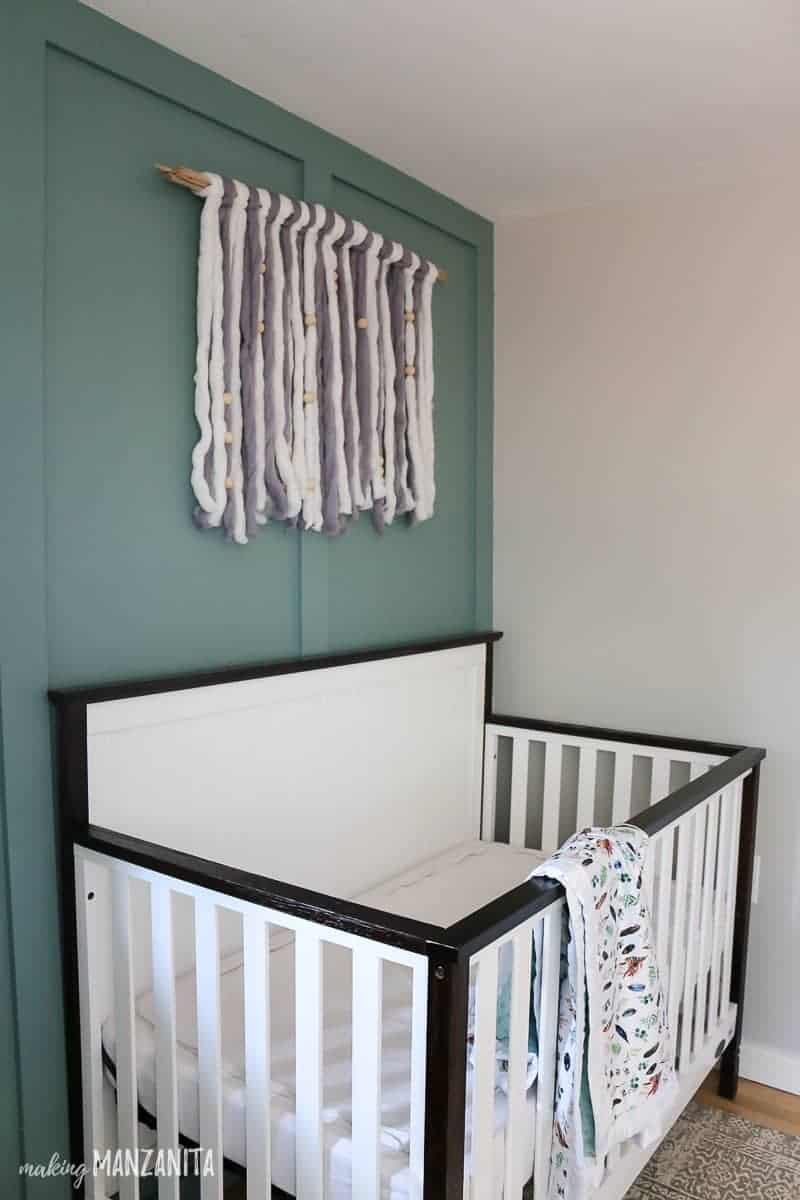 White crib with yarn wall hanging above it