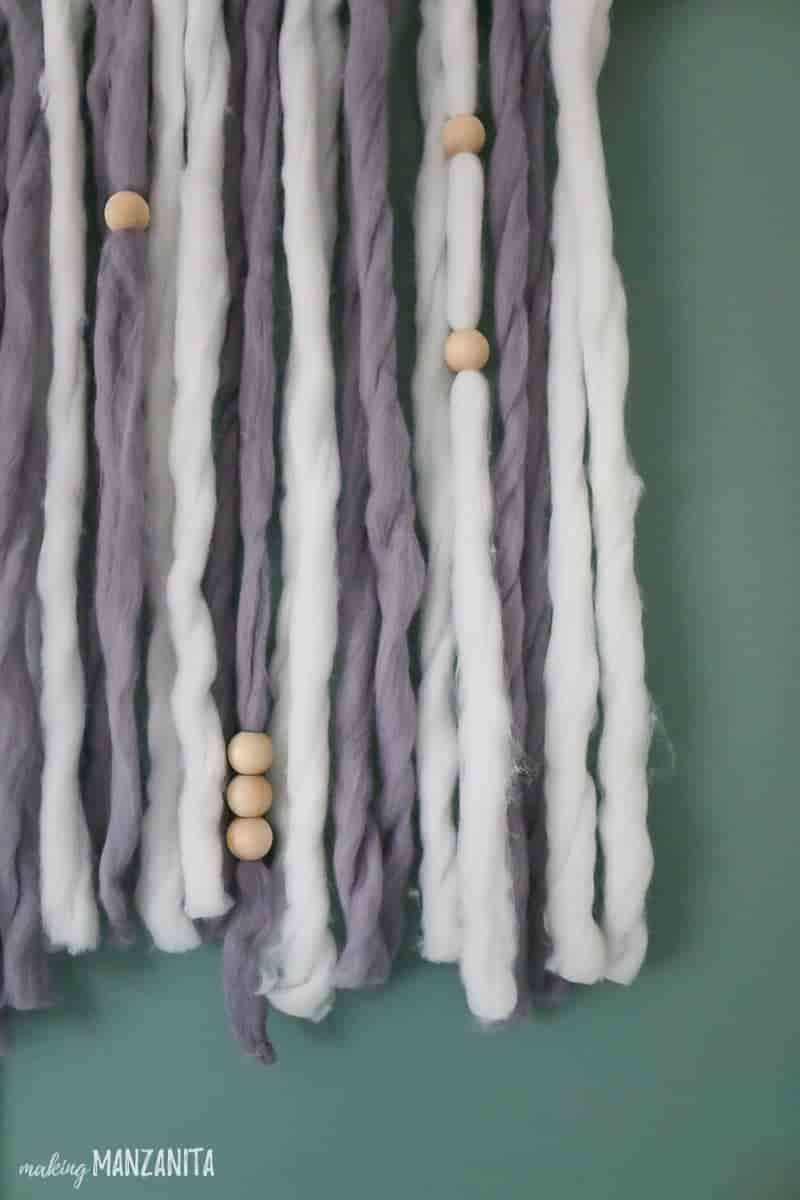 Close up shot of boho style yarn hanging with wood beads