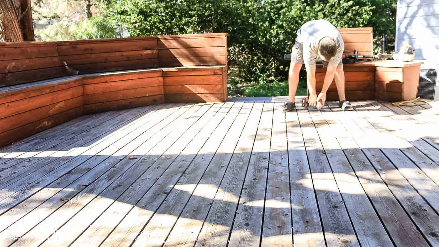 Man tightening screws on wood decking