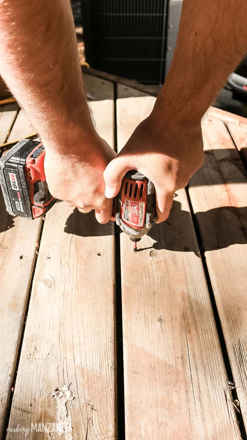 Man tightening screws with drill on wood deck
