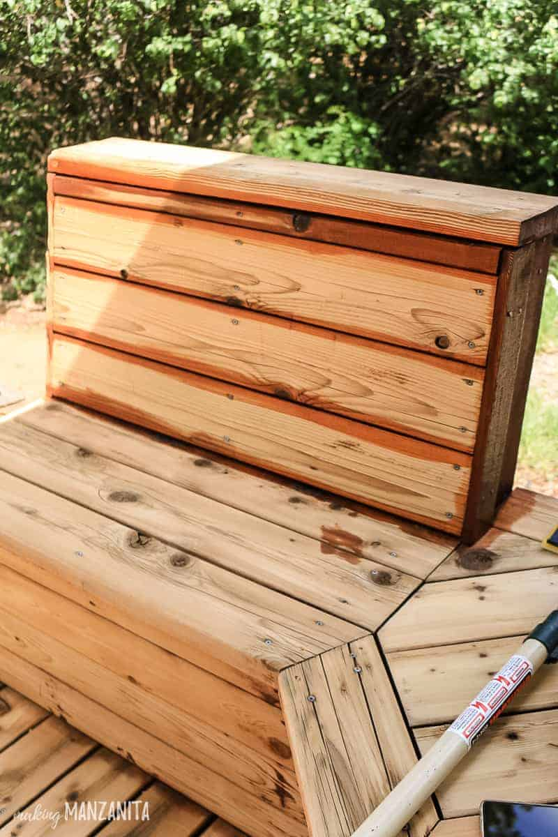 Applying oil finish to upright pieces of the back of the bench on wood deck