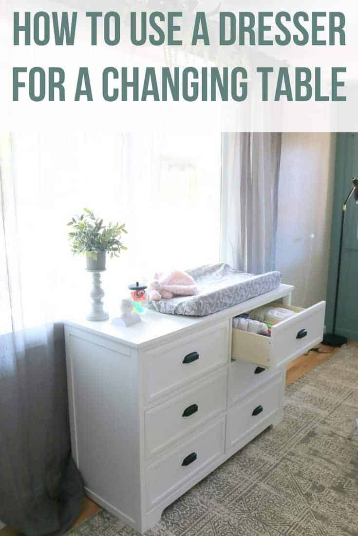 White dresser in front of window with changing pad on top and top drawer opened with text overlay that says how to use a dresser for a changing table