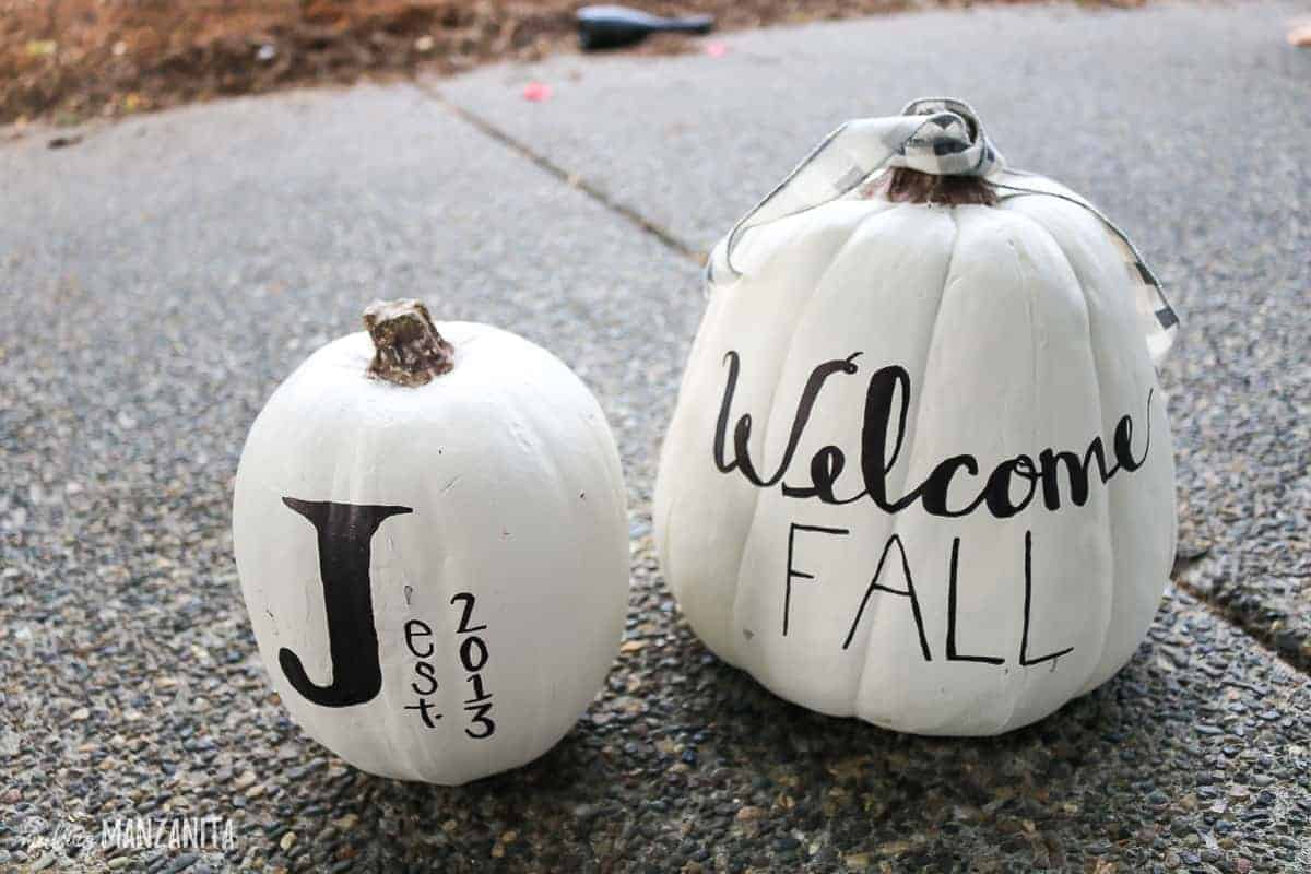 White painted craft pumpkins with sharpie drawn designs. One on left has a big J and says est. 2013 and the other says Welcome Fall