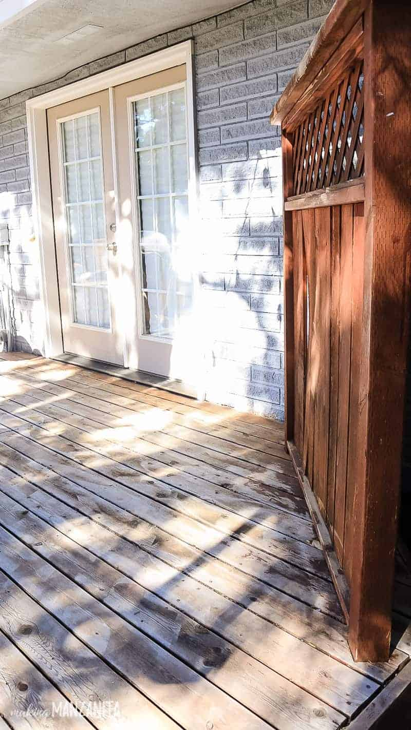 Deck that needs to be refinished with tan french doors